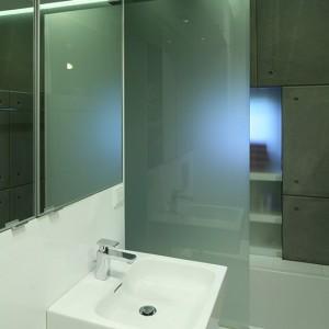 Parawan z mlecznego szkła chroni łazienkę przed zachlapaniem, zapewniając też intymną zasłonę. Natomiast duże lustra – umieszczone na całej długości ściany nad płytami z betonu oraz nad umywalką – optycznie  powiększają niewielką przestrzeń. Fot. Bartosz Jarosz.