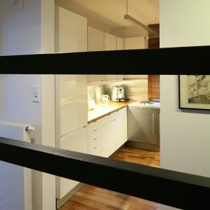 W kuchni zrezygnowano z drzwi i częściowo zlikwidowano ściankę działową, nadając jej półotwarty charakter. Takie rozwiązanie optycznie powiększyło nie tylko kuchnię, ale i hol. Fot. Bartosz Jarosz.