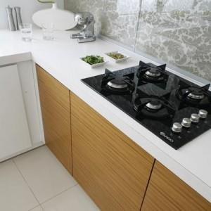 Przestrzeń między blatem roboczym a szafkami górnymi wypełnia tapeta za szkłem, która jest właściwie jedynym ornamentem w przestrzeni kuchennej. Proj. Małgorzata Mazur.