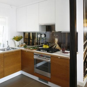 Fototapeta, z motywem zapowiedzianym w korytarzu, pojawia się w kuchni za szkłem między szafkami. Bawiąca oko, graficzna alternatywa dla płytek. Proj. Małgorzata Mazur.