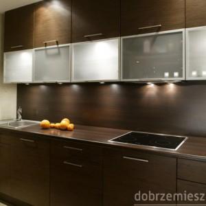 Z perspektywy salonu kuchenna zabudowa wygląda niczym elegancka, nowoczesna meblościanka. Ten efekt osiągnięto dzięki nadaniu frontom szafek, blatowi roboczemu oraz ścianie nad nim jednolitej, ciemnobrązowej barwy, odpowiadającej kolorystyce mebli w części wypoczynkowej mieszkania. I choć szafki są wykonane z drewna wenge (zmodyfikowane przez architekta meble firmy Stolmar), a blat i ściana z laminowanej płyty, dla laika ta różnica jest właściwie nieuchwytna. Proj. Jarosław Jończyk i Monika Włodarczyk.