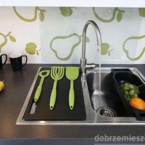 Tapetę w kuchennej przestrzeni międzyszafkowej przesłaniają szklane tafle, zamontowane jedynie w miejscach niezbędnych, np. przy zlewozmywaku. Proj. Jolanta Kwilman.