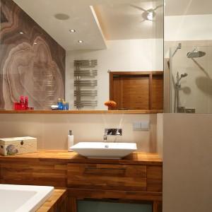 Elementy wyposażenia - zarówno wanna, jak i umywalka (maki Kohler) oraz półka lustra – tworzą wielopoziomową, rozrzeźbioną konstrukcję oprawioną w drewno tekowe. Fot. Bartosz Jarosz.