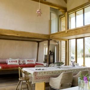 Nietypowa konstrukcja domu z otwartą przestrzenią i galerią na piętrze kosztowała właścicieli pięć lat oczekiwania na zezwolenie na budowę. Ale oboje twierdzą, że było warto. Uwagę zwraca tu przede wszystkim łóżko – rzadko spotykany widok w pokojach dziennych. Zakupione przez właścicieli w czasie ich podróży poślubnej na Bali, jest teraz prawdziwym centrum życia rodzinnego. Fot. Polly Eltes/Narratives.