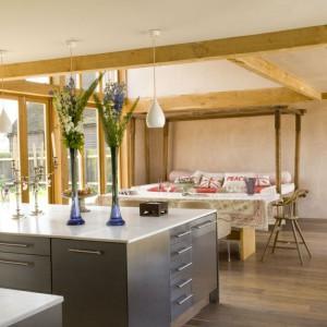 Parter domu to jedna ogromna przestrzeń, którą symbolicznie wydzielają jedynie drewniane belki sufitowe. Użycie drewna ociepliło wnętrze i dodało mu nieco rustykalnego charakteru. Fot. Poly Eltes/Narratives.