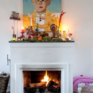 Nad kominkiem dumnie zawisł portret króla Tajlandii. Kolekcja na kominkowym gzymsie to dzieło całej rodziny – co roku przybywa do niej coś nowego. Fot. Sian Williams/Narratives.