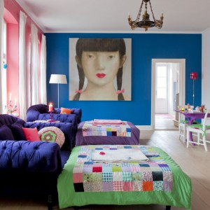 Zjawiskowy portret dziewczyny wiszący w salonie również został kupiony w Tajlandii. To właśnie stamtąd Charlotte czerpie mnóstwo inspiracji do swoich projektów. Granatowe kanapy są kolejnym wyrazistym elementem tego wnętrza – właścicielka nie bała się zestawić z nimi kolorowych narzut i ścian w odważnych barwach. Fot. Sian Williams/Narratives.