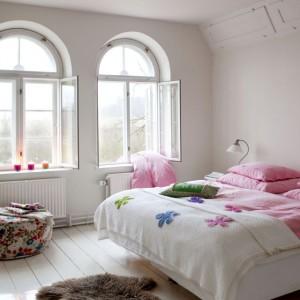 Sypialnia gospodarzy jest nieco bardziej wyciszona kolorystycznie. Główną rolę odgrywają w niej delikatne pastele. Więcej barw wnoszą do tego spokojnego wnętrza wzorzyste pufy. Fot. Sian Williams/Narratives.