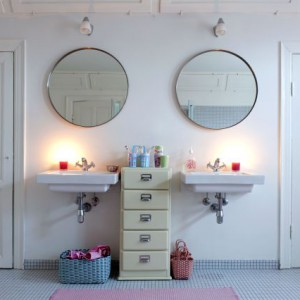 Cytrynowa szafka w stylu lat 30. oddziela od siebie dwie proste umywalki wprowadzając nieco koloru do wnętrza. Fot. Sian Williams/Narratives.