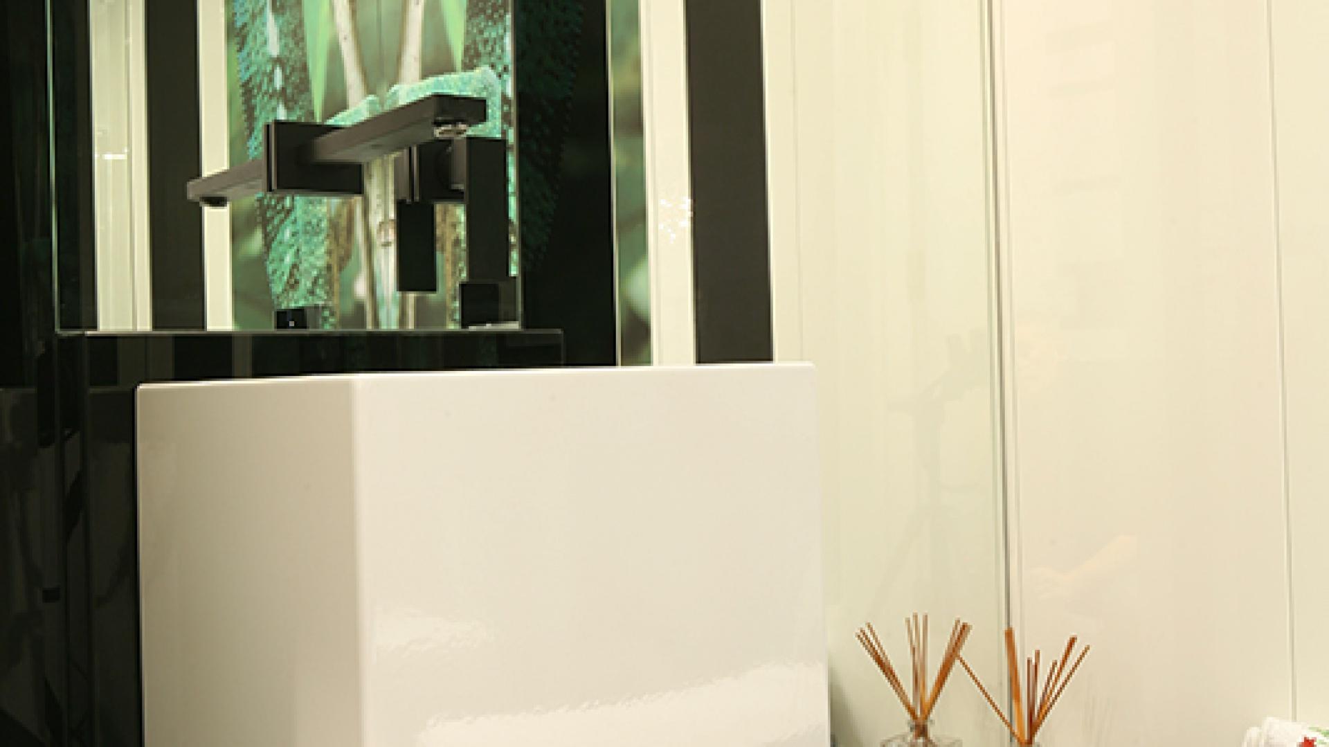 Aranżacja wnętrza utrzymana jest w czarno-białej kolorystyce. Poziome pasy z czarnego szkła Lacobel to nawiązanie do dekoracyjnego motywu pasów, który pojawia się w całym domu. Oświetlenie marki Lira. Fot. Bartosz Jarosz.