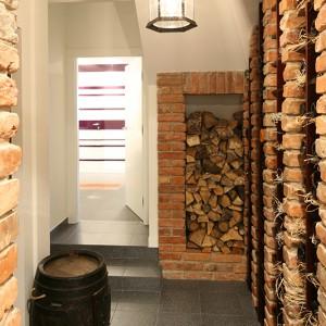 Gdy ogień w kominku przygasa, można podłożyć drew nie wychodząc z domu. Jego zapas przechowuje się w specjalnie zaprojektowanej wnęce w holu, stylowo wykończonej cegłami. Fot. Bartosz Jarosz.