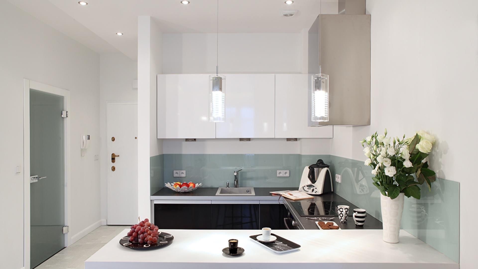 Czerń i biel zabudowy kuchennej doskonale ze sobą współgrają. W ten zgrany duet wpisują się zarówno metaliczne dodatki, jak i szklane tafle nad blatem roboczym. Fot. Monika Filipiuk-Obałek.