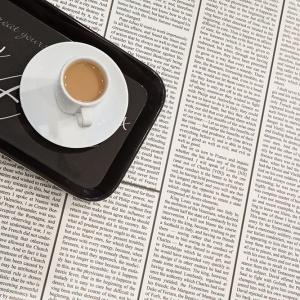 """Zawsze jest co poczytać przy kawie... Podłoga wykończona panelami laminowanymi z kolekcji """"Trendtime 2"""" firmy Parador. Wzór """"Letters White"""" to przeniesienie na dekor zadrukowanych stron książki. Fot. Monika Filipiuk-Obałek."""