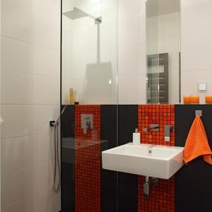 """Funkcjonalny charakter łazienki zapewnia otwarta wnęka prysznicowa z odpływem w posadzce (wypełnienie rusztu: okładzina ceramiczna). Prysznic od reszty pomieszczenia oddziela tafla szkła, sięgająca aż do sufitu. Zastaw natryskowy z serii """"160"""" marki Steinberg. Proj. Monika Filipiuk-Obałek."""
