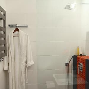 Wykończona mozaiką oraz czarnymi płytkami zabudowa instalacji podtynkowej oferuje praktyczną półkę. W strefie kąpielowej dodatkowo umieszczono także praktyczny reling. Proj. Monika Filipiuk-Obałek.