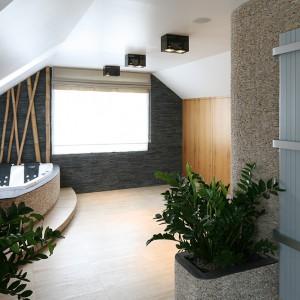Przestronna łazienka to  domowe centrum relaksu, a także garderoba (szafy po prawej). Duża ilość światła  dziennego oraz naturalne materiały okładzinowe dają wrażenie przestronności i świeżości. Obok wejścia – grzejnik  dekoracyjny marki Vasco. Fot. Bartosz Jarosz.