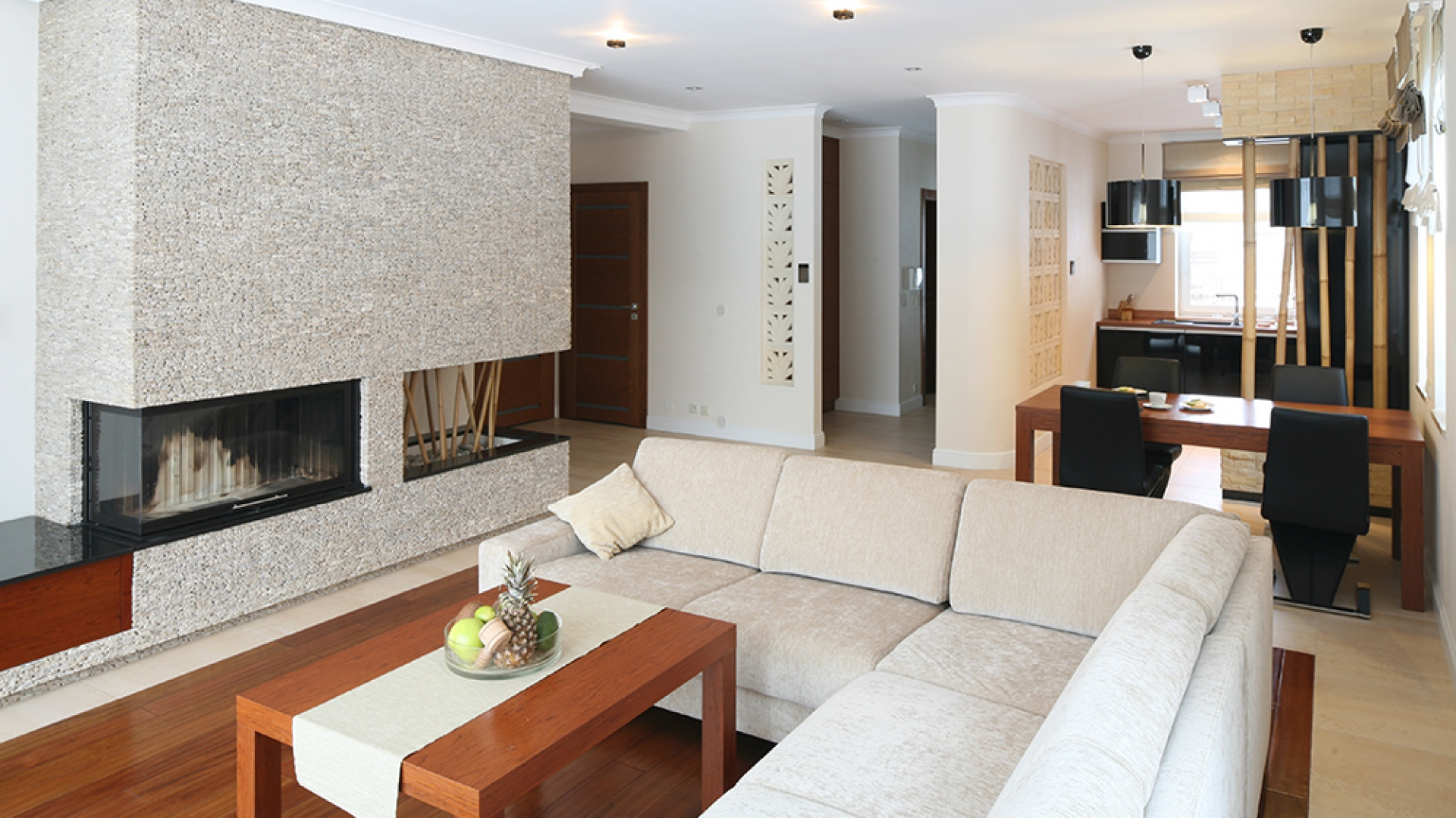 Kominek o sporej bryle organizuje przestrzeń salonu, dodaje ciepła i tworzy naturalny klimat, co podkreśla okładzina z kamienia. Fot. Bartosz Jarosz.