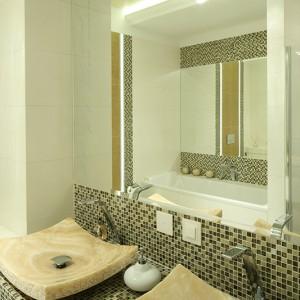 Niewątpliwą perełką aranżacji łazienki są dwie onyksowe umywalki pochodzące wprost z Indonezji. Umieszczone na blacie mienią się złotem mozaiki. Fot. Bartosz Jarosz.