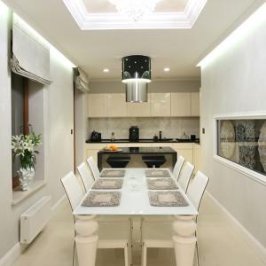 Jadalnia utrzymana została w niemalże czystej bieli. Szklany stół i skórzane krzesła podkreślają jej nowoczesny charakter. Ozdobna wnęka,  pomysłu projektantki, przypomina, iż to wnętrze oryginalne i niepowtarzalne. Fot. Bartosz Jarosz.