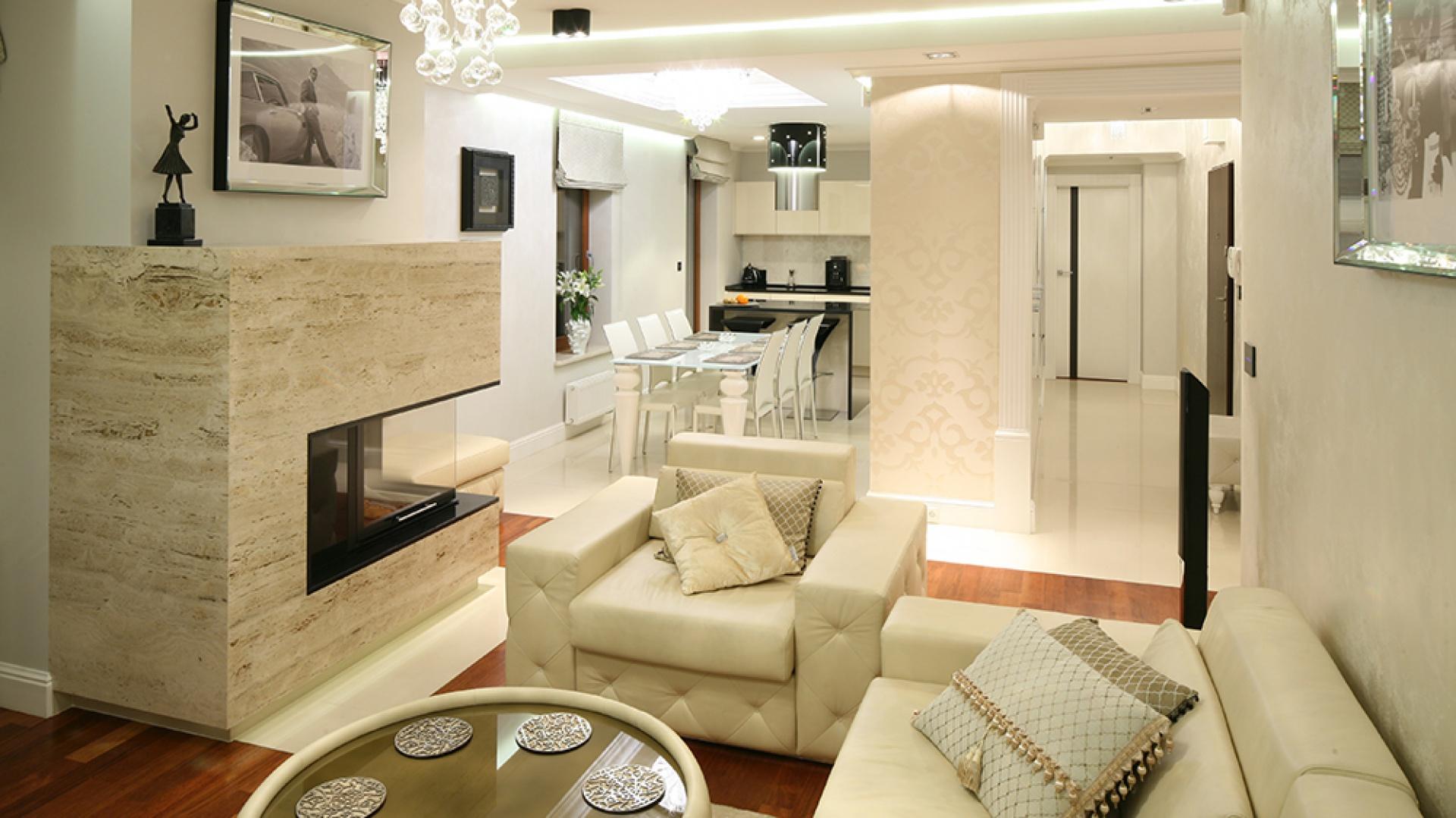 Kuchnia wtapia się w piaskowo-białą kolorystykę apartamentu. Z perspektywy salonu wzrok przyciąga biżuteryjny okap będący jednocześnie lampą. Fot. Bartosz Jarosz.