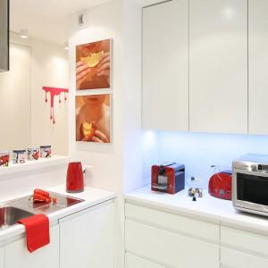 Kuchnia jest nieduża, ale funkcjonalna. Proste, minimalistyczne meble, wykonane z MDF-u lakierowanego na wysoki połysk w białym kolorze, wyposażono w bezuchytowe systemy otwierania. W wysokiej zabudowie ukryto lodówkę marki Bosch. Fot. Bartosz Jarosz.