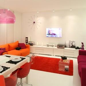 Wnętrze skąpane w bieli ożywiają dodatki w mocnych, intensywnych kolorach. Czerwień doskonale dogaduje się z tu z pomarańczą oraz różem. Fot. Bartosz Jarosz.