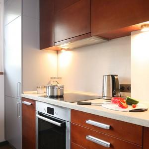 Zabudowa kuchenna stanowi połączenie zarówno dwóch różnych kolorów, jak i materiałów. Szary lakierowany MDF doskonale dogaduje się z  laminatem o barwie orzecha. Tynk strukturalny imitujący beton zabezpiecza ściany nad blatem roboczym. Fot. Bartosz Jarosz.