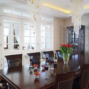 Jadalnię od pozostałych pomieszczeń oddzielają duże, szklane drzwi w białym kolorze. Kryształowe żyrandole w złotych oprawach dumnie zwisają ze zdobionego sufitu, podświetlonego ledowymi wężami. Fot. Monika Filipiuk-Obałek.