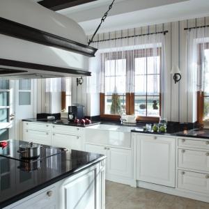 Zabudowa kuchenna (malowane, lakierowane drewno) wykonana została z dbałością o  charakterystyczne dla stylu dekoracyjne detale. Do frezowanych frontów dobrano efektowne porcelanowe gałki. W osobnym pomieszczeniu (po lewej) znajduje się spiżarnia. Fot. Monika Filipiuk-Obałek.