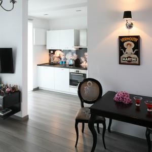 Minimalistyczne tło dla stylowej aranżacji salonu stanowi prosta, nowoczesna zabudowa kuchenna. Fot. Bartosz Jarosz.