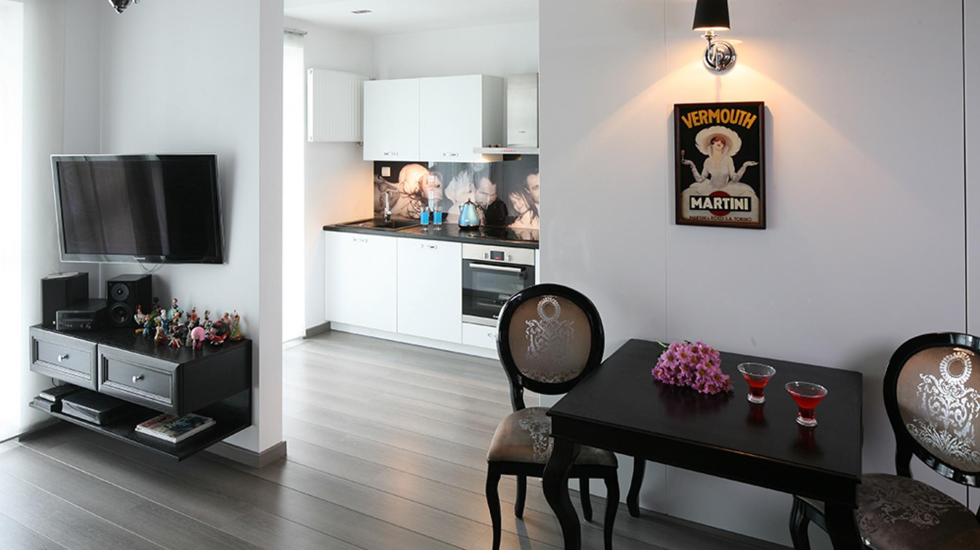 Kuchnia sąsiaduje z salonem, gdzie zaaranżowano również niewielką, ale stylową jadalnię. Jednolita podłoga (panele laminowane z oferty Vip Parkiet) we wszystkich pomieszczeniach podkreśla otwarty charakter strefy dziennej. Fot. Bartosz Jarosz.