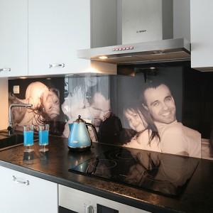 Wyposażenie strefy gotowania i pieczenia to płyta grzejna, piekarnik oraz okap marki Bosch. Ścianę na blatem dekoruje umieszczone za taflą poliwęglanu zdjęcie w dużym formacie. Fot. Bartosz Jarosz.
