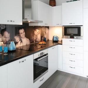 Na każdym kroku można przekonać się o indywidualnym charakterze wnętrza: do oryginalnego wykończenia ściany nad blatem wykorzystano zdjęcia z rodzinnego albumu. Fot. Bartosz Jarosz.