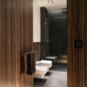 W dużej, wygodnej łazience z dwom umywalkami, połączone zostały wszystkie materiału użyte we wnętrzu: drewno, fornir i MDF w połysku.  Zestawienie ich z płytkami gresowymi oraz dekoracyjną mozaiką, zastosowaną w kabinie prysznicowej, dodatkowo wzmacnia szyk tej kąpielowej  przestrzeni. Fot. Bartosz Jarosz.