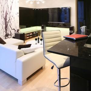 Kuchnia i salon stanowią wspólną przestrzeń także pod względem zastosowanej kolorystki oraz materiałów wykończeniowych. Fot. Bartosz Jarosz.