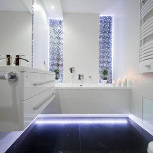 """Efektowne oświetlenie podkreśla urok okładzin ceramicznych, nadaje też łazience niepowtarzalny charakter. Także ergonomiczne podcięcie w obudowie wanny zostało podświetlone: światło zjawiskowo odbija się w podłodze wykończonej płytkami gresowymi """"Cafe"""" w kolorze czarnym Ceramica Adorno. Fot. Marta i Michał Rudiak."""