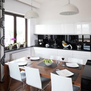Białe meble kuchenne wykonane z MDF-u lakierowanego na wysoki połysk stworzyły elegancki duet z czarnym kamiennym blatem oraz ścianą nad blatem zabezpieczoną szkłem lacobel, również w kolorze czarnym. Fot. Bartosz Jarosz.