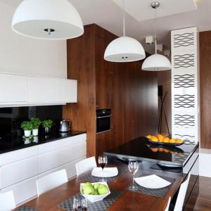Symboliczną granicę między kuchnią a salonem wyznacza podwieszony sufit, elegancka lśniąca wyspa oraz fornirowany orzechowy stół, pełniące jednocześnie funkcję jadalni. Fot. Bartosz Jarosz.