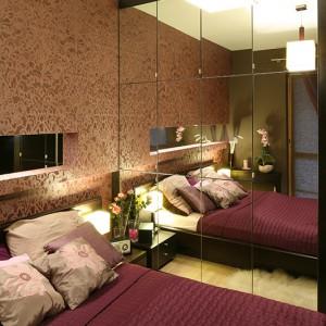 W sypialni poza dużym łóżkiem zmieściła się także pojemna szafa, pełniąca rolę garderoby. Jej szklane fronty ocieplają drewniane wykończenia. Fot. Bartosz Jarosz.