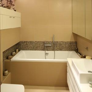 Przytulna, funkcjonalna łazienka skąpana jest w beżach i brązach. Ciekawym, ożywiającym akcentem jest fototapeta na ścianie. Fot. Bartosz Jarosz.