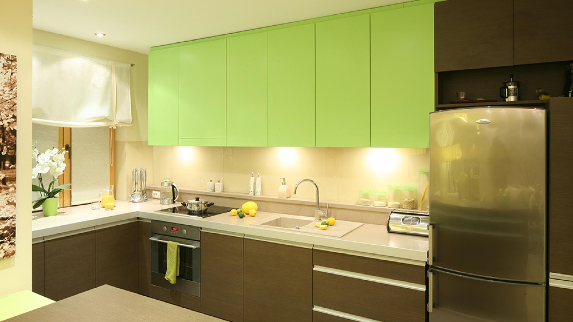 Prosta, reprezentacyjna zabudowa kuchenna wykonana z MDF-u tryska energią. Górne szafki w kolorze wesołej limonki, uspokajają dolne w kolorze ciepłego drewna. Jasny blat dopełnił całość. Fot. Bartosz Jarosz.
