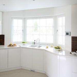 """Kuchnia z wykuszowym oknem jest jasna i funkcjonalna. Prosta forma zabudowy oraz białe fronty z MDF-u i blat z kompozytu odpowiadają za nowoczesny charakter zabudowy, który """"temperuje"""" fornir palisandru. Fot. Bartosz Jarosz."""
