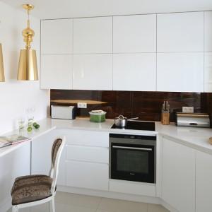"""Przedłużenie blatu roboczego pełni rolę barku śniadaniowego. Stylowe krzesło oraz lampy w złotym kolorze (""""Josephine"""" Metalarte) nawiązują do aranżacji salonu i jadalni, a nowoczesnej  kuchni dodają uroku. Fot. Bartosz Jarosz."""
