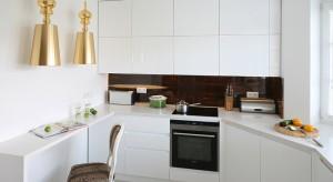 Nowoczesna kuchnia może być także stylowa. Aby śnieżnobiała zabudowa kuchenna nie wyziębiła wnętrza, dodano ognisty fornir palisandru i gorące złoto.