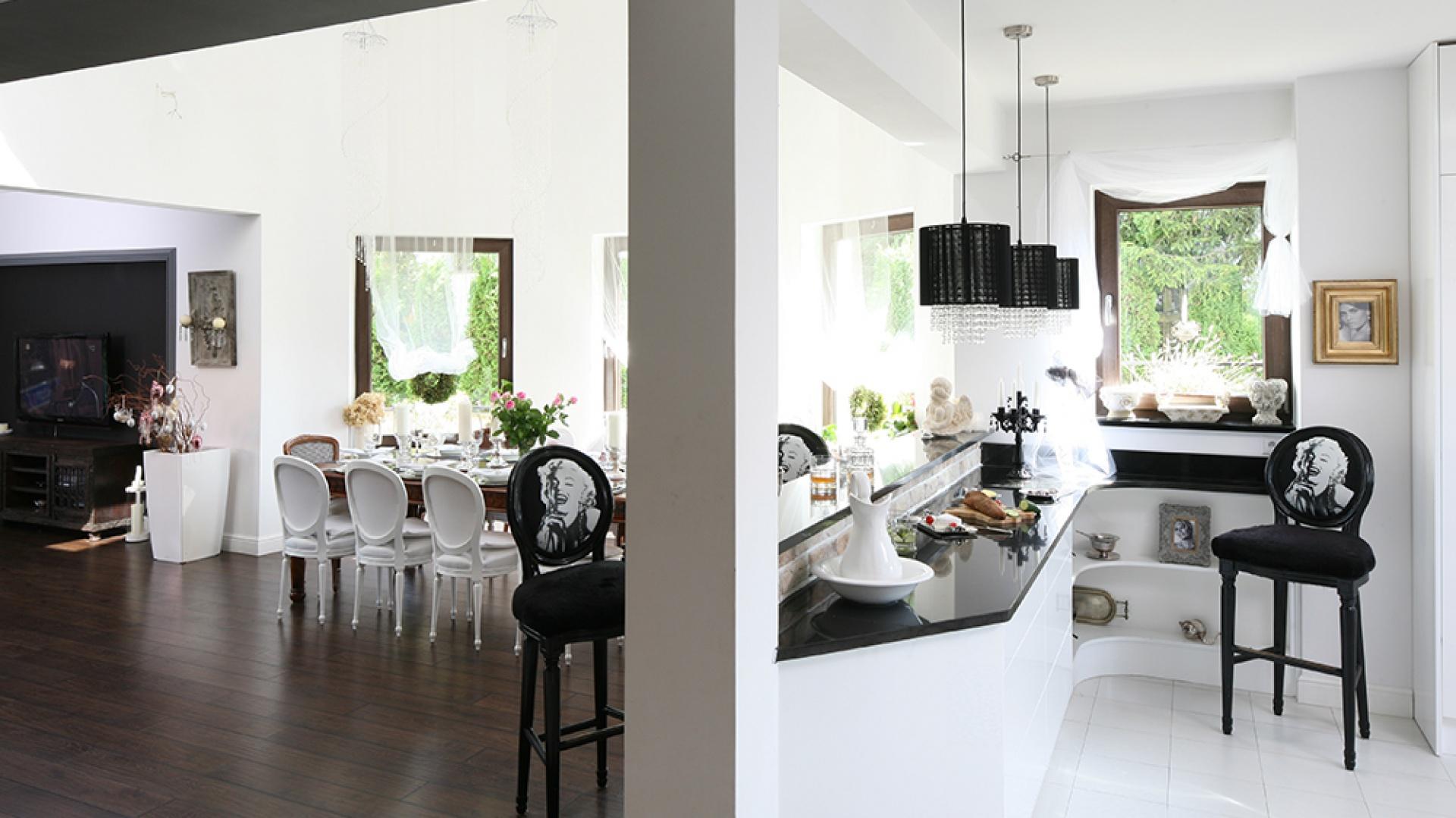 Od strony kuchni strefa barowa zmienia charakter na bufetowo-kredensową. Pod blatem są szuflady na akcesoria stołowe. Fotosy Marilyn Monroe na hokerach kreują lekką, niezobowiązującą atmosferę. Fot. Bartosz Jarosz.