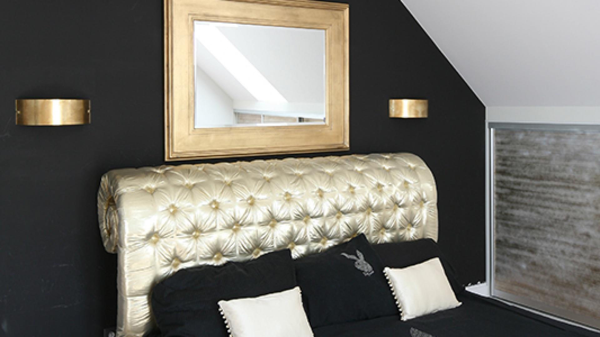 Na czarnej ścianie wyśmienicie prezentuje się lustro w masywnej, złotej ramie oraz kinkiety. Wyeksponowane jest także pikowane wezgłowie łóżka, które właścicielka sama zaprojektowała. Projekt: Magdalena Konochowicz. Fot. Bartosz Jarosz
