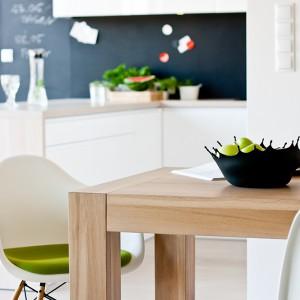 """Otwarta kuchnia sąsiaduje z jadalnią, której wyposażenie stanowi niezobowiązujący lecz efektowny zestaw: stół """"Manu""""wykonany przez Manufakturę Drewna oraz krzesła  """"DAW"""" marki Vitra. (proj. Charles&Ray Eames; 1950 r.) z oferty Ipnotic Design Store. Fot. Rafał Owczarski."""