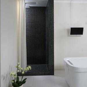 Wnęka prysznicowa, zgodnie z życzeniem inwestorki, nie została zamknięta drzwiami, a przesłonięta kotarą; wykończona mozaiką szklaną z oferty Trend, armatura Hansgrohe. Fot. Bartosz Jarosz.