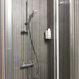"""We wnęce prysznicowej zainstalowano baterię Hansgrohe """"Ecostat 1001"""" w zestawie z drążkiem i słuchawką prysznicową. Składane do wewnątrz drzwi wybrano z serii """"Swing Line"""" SanSwiss. Fot. Bartosz Jarosz."""