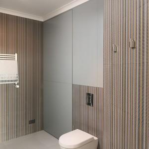 Gospodarcze funkcje pomieszczenia ukryto we wnękach: po lewej – pralka, kosz na bieliznę, wyżej – półki na detergenty, pośrodku – półki nad spłuczką, po prawej – szafa na akcesoria do sprzątania. Wszystkie zamknięte frontami z MDF-u wykończonego szarym, matowym lakierem; otwieranie przez naciśnięcie (wykonawca mebli: 4Home-&Kitchen – przedstawiciel Mebel RUST w woj. podlaskim; zespół: arch. wnętrz Weronika Giżewska, arch. wnętrz Magdalena Beszterda, menedżer projektu Piotr Zubrycki). Fot. Bartosz Jarosz.